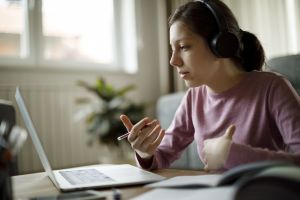 Teenage girl with headphones having online school class at home