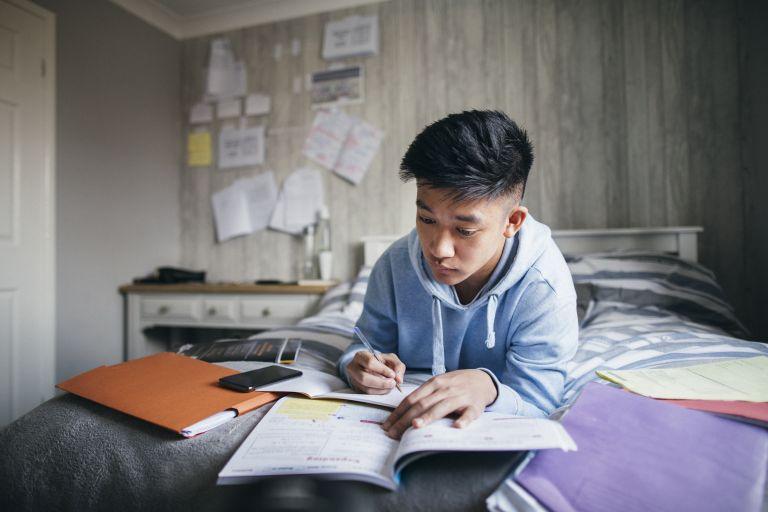Teenage boy lying on his bed while concentrating on homework for his exams.